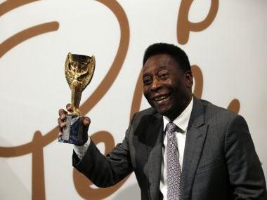 Pele holds a replica Jules Rimet trophy. AFP