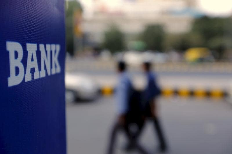 Commuters walk past a bank sign along a road in New Delhi in this November 25, 2015 file photo. REUTERS/Anindito Mukherjee/Files