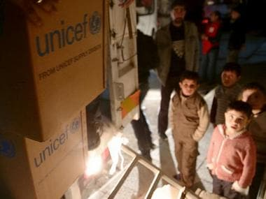 Boys watch unloading of humanitarian aid in the rebel held besieged town of Kafr Batna, on the outskirts of Damascus, Syria. File Photo. Reuters