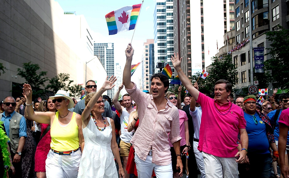 (Left to right) Ontario Premier Kathleen Wynne, Prime Minister Justin Trudeau and Toronto Mayor John Tory march with tens of thousands of people in Toronto's Gay Pride parade. Photo Courtesy: AP