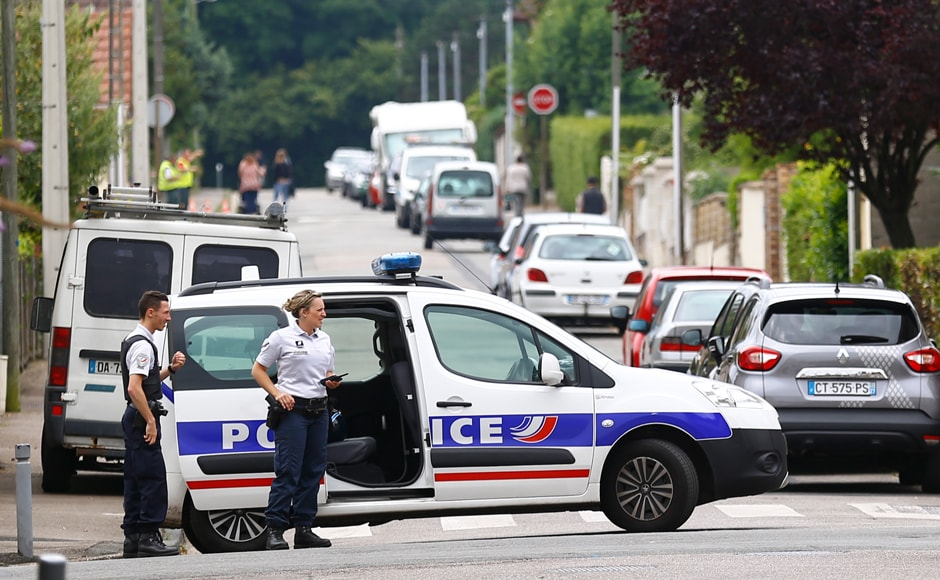 French police officers prevent the access to the scene of an attack in Saint Etienne du Rouvray, Normandy, France, Tuesday, 26 July, 2016. Two attackers invaded a church Tuesday during morning Mass near the Normandy city of Rouen, killing an 84-year-old priest by slitting his throat and taking hostages before being shot and killed by police, French officials said. AP/Francois Mori