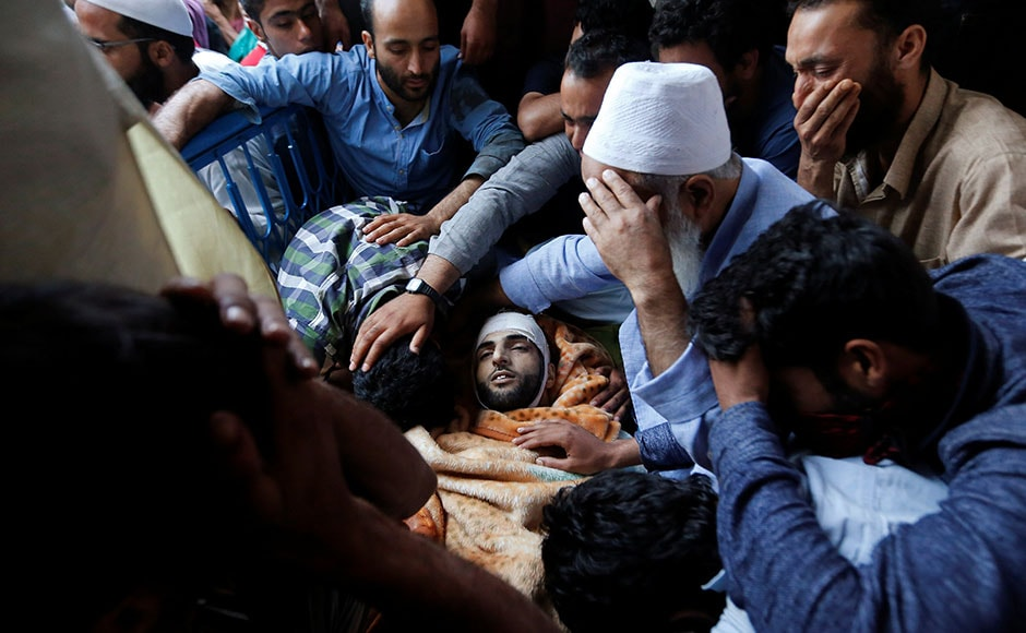 Family members and relatives mourn next to Wani's body. Burhan, who carried a cash reward of Rs 10 lakh on his head, is believed to have taken up the gun to avenge his elder brother's humiliation by security forces who made him do squats after picking him up for no crime. Reuters