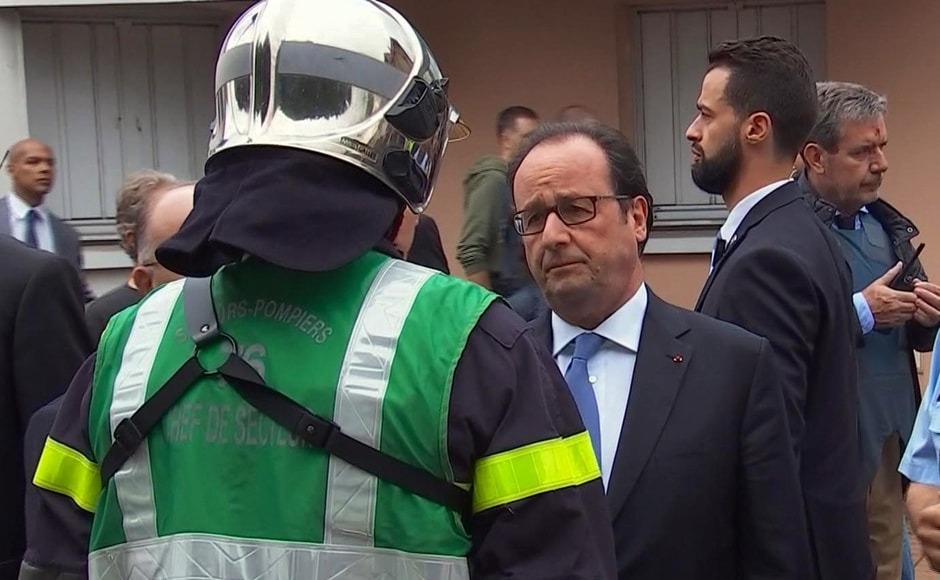 In this grab made from video, French President Francois Hollande speaks with emergency services personnel after arriving at the scene of the hostage situation in Normandy, France, Tuesday, 26 July, 2016. Two attackers took hostages inside a French church during morning Mass on Tuesday in the Normandy town of Saint-Etienne-du-Rouvray, killing an 86-year-old priest by slitting his throat before being shot and killed by police, French officials said. The Islamic State group claimed responsibility for the attack. AP