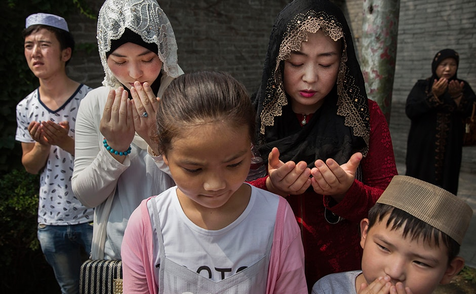 A Chinese Hui Muslim family prays at the 'Sheiks Tombs'. China's constitution provides for Islam as one of five 'approved' religions in the officially atheist country though the government enforces severe limits. Worship is permitted only at state-sanctioned mosques and proselytizing in public is illegal. Getty images.