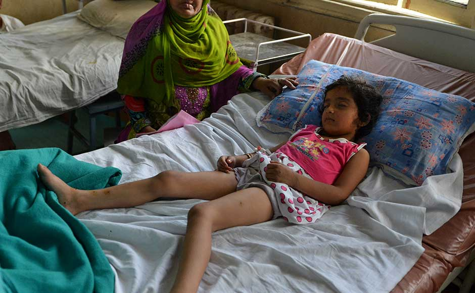 Five year-old Zohra Zahoor, who has pellet wounds in her legs, forehead and abdomen, sleeps on a hospital bed as her aunt Naseema Jan looks on, at a hospital in Srinagar on July 13, 2016. According to Naseema Jan, pellets were fired from a police vechile at members of the family as they stood outside their home. Hospitals in Kashmir are overwhelmed, with hundreds of wounded patients pouring in as the region reels from days of clashes between anti-India protesters and government troops.