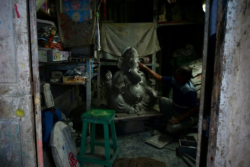 A sculptor in Mumbai works on an idol in preparation for Ganesh Chaturthi. Image by Mobeen Ansari