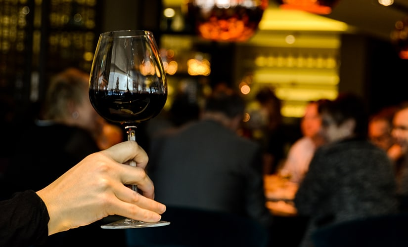 A glass of wine in a restaurant. Google