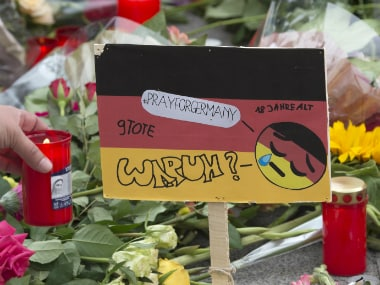 A woman lights a candle besides a sign painted in the colors of German flag besides the Olympia shopping center in Munich on Saturday. The word down reads: 'Why?'. AP