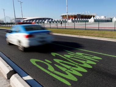 A police car passes at the Olympic lane in front of the Olympic park in Rio de Janeiro. Reuters