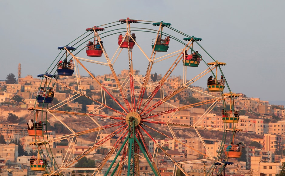 People ride a Ferris wheel in an amusement park as they celebrate the first day of the Muslim holiday of Eid al-Fitr, which marks the end of the holy month of Ramadan at the port-city of Sidon, southern Lebanon. Reuters
