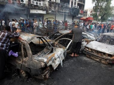 People inspect the site of a suicide car bomb in the Karrada shopping area, in Baghdad. Reuters