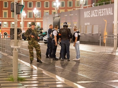"""Police officers and a soldier stand by the sealed off area of an attack after a truck drove on to the sidewalk and plowed through a crowd of revelers who'd gathered to watch the fireworks in the French resort city of Nice, southern France, Friday, July 15, 2016. A spokesman for France's Interior Ministry says there are likely to be """"several dozen dead"""" after a truck drove into a crowd of revelers celebrating Bastille Day in the French city of Nice. (AP Photo/Ciaran Fahey)"""