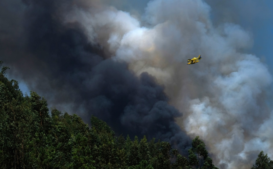 A firefighting airplane flies above a forest fire near Mortagua, northern Portugal on Thursday. Firefighters in Portugal are battling multiple blazes fed by brush in a hot, dry summer for a sixth straight day. A full 186 wildfires were counted Wednesday on Portugal's mainland. The fires, which are also ravaging southern France, have killed at least four people, burning scores of homes and forcing the evacuation of thousands, including tourists. AP