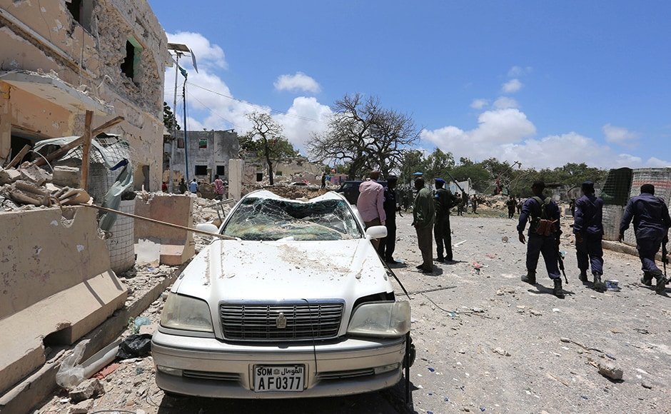 The massive blast left a trail of destruction across the hilltop presidential complex and to nearby hotels. The bombing tore into blast walls protecting hotels and blew off the roofs of nearby houses. Somali government forces walk past a car destroyed as they arrive to secure the scene of the bombing. Reuters