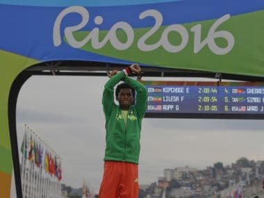 Ethiopia's Feyisa Lilesa, crosses his arms as he celebrates on the podium after the men's marathon. AP