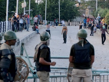 Srinagar: Youths defy curfew and throw stones on Security forces during clashes . PTI