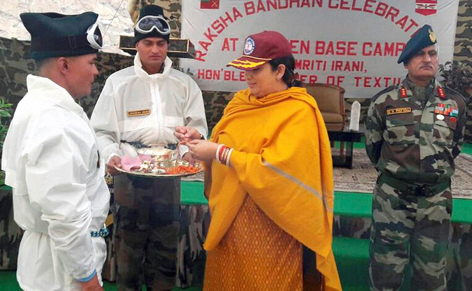 "Textiles Minister Smriti Zubin Irani tying Rakhis on the wrists of Indian Army jawans on the occasion of ""Raksha Bhandan"" at Siachen Glacier on Thursday. PTI Photo (PTI8_18_2016_000188B)"