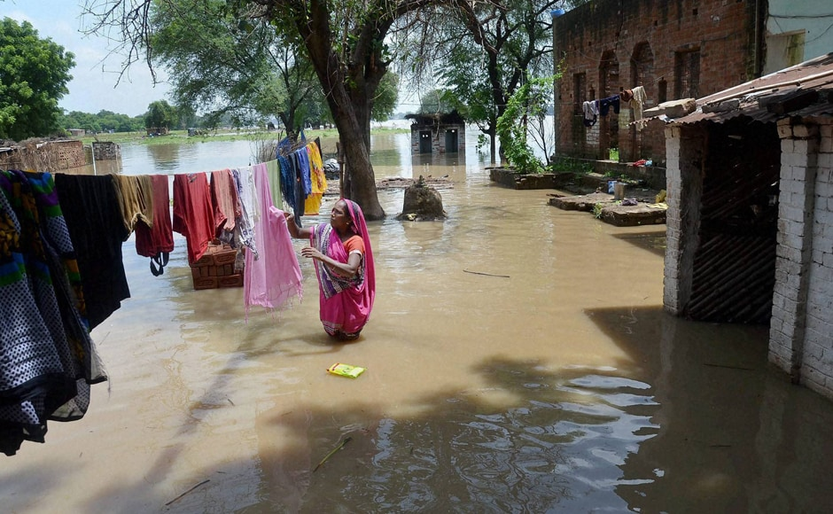 Incessant rains in many parts of Uttar Pradesh have resulted in floods. A woman can be seen drying clothes in a flooded area in Mirzapur. Six persons of a family were killed in the area when the car they were travelling fell into an overflowing drain. Photo: PTI