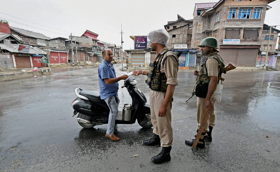 A security jawan checks the identification details of a Kashmiri as restrictions have been imposed on movements of common people in the Valley . PTI