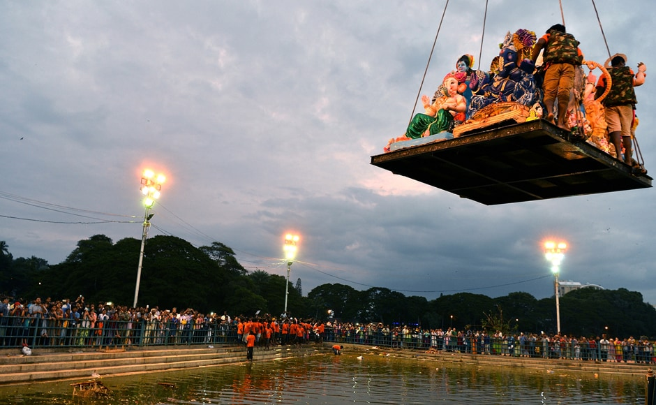 Volunteers are lowered on a platform with large idols of Ganesh brought by Hindu devotees for immersion at a water tank in Bangalore. (Photo courtesy: AFP)