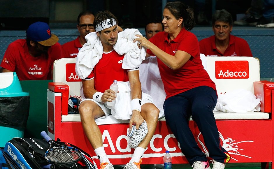 Spanish tennis player Conchita Martinez puts a wet towel on compatriot David Ferrer as he rests between sets during his Davis Cup men's tie match against India's Saketh Myneni in New Delhi, India, Friday, Sept. 16, 2016. (AP Photo/Saurabh Das)
