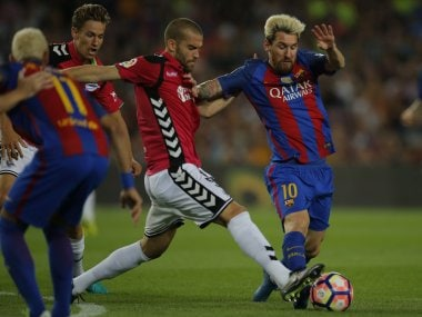 FC Barcelona's Lionel Messi duels for the ball against Alaves's Victor Laguardia. AP