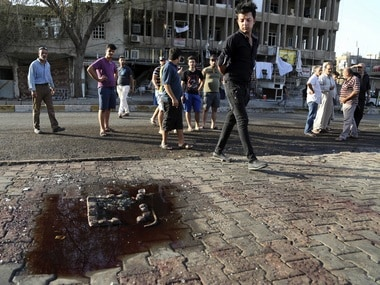 A car bombing in a bustling commercial area at Karradah neighborhood has killed and wounded civilians. People watch gather around a blood stain left after the incident. AP