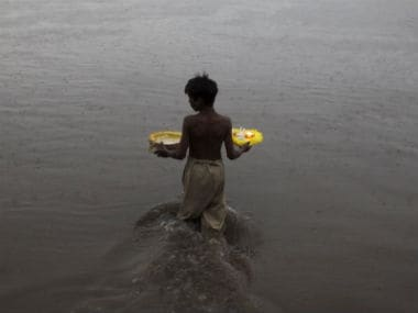 A boy enters river Ravi to release oil lamps and candles in water. Reuters