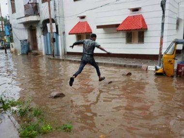 A man tries to cross a waterlogged street in Hyderabad. PTI