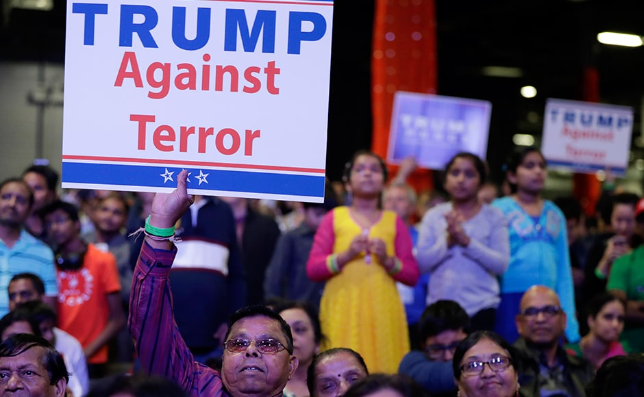 Supporters of Trump hold up signs. Trump gave India BFF status and praised Narendra Modi. AP