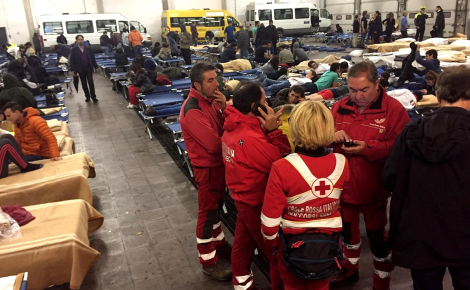 Rescuers attend people sheltered in a bus hangar in Camerino, central Italy, Thursday, Oct 27, 2016, following an earthquake that hit the area. A pair of strong aftershocks shook central Italy late Wednesday, crumbling churches and buildings, knocking out power and sending panicked residents into the rain-drenched streets just two months after a powerful earthquake killed nearly 300 people. (Roberto Alimonti/ANSA via AP)