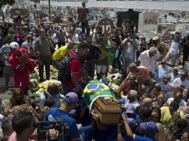 People gather around the flag draped coffin of Carlos Alberto Torres during his burial. AP