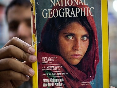 FILE - In this file photo taken on Wednesday, Oct. 26, 2016, the owner of a book shop shows a copy of a magazine with the photograph of Afghan refugee woman Sharbat Gulla, from his rare collection in Islamabad, Pakistan. A Pakistani prosecutor said Wednesday, Nov. 2, 2016 that a court has dismissed a bail plea from National Geographic's famed green-eyed 'Afghan Girl,' arrested a week ago over allegedly forged ID papers. (AP Photo/B.K. Bangash, File)