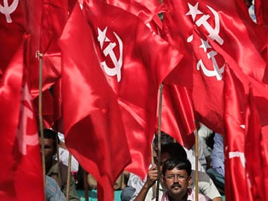 An activist from the Communist Socialist Unity Centre of India (SUCI) sits under his party's flags during a protest in New Delhi March 14, 2012. Thousands of activists on Wednesday protested against the rising prices of essential commodities and corruption, activists said. REUTERS/Adnan Abidi (INDIA - Tags: CIVIL UNREST POLITICS)