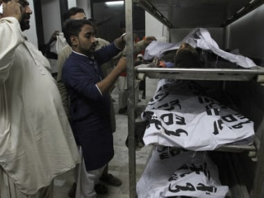 People identify the bodies, victims of a bomb blast at a Sufi shrine, at a morgue of a local hospital in Karachi in Pakistan. AP