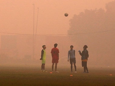 Boys playing football on a smoggy morning in New Delhi on Wednesday. Reuters