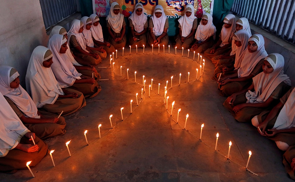 School girls light candles in the shape of a ribbon during a HIV/AIDS awareness campaign ahead of World Aids Day, in Ahmedabad, India November 30, 2016. The WHO report cites worrying numbers, when it comes to awareness about the disease in young girls. Fewer than one in every five girls between 15 years and 19 years of age are aware of their HIV status, the report said. Reuters