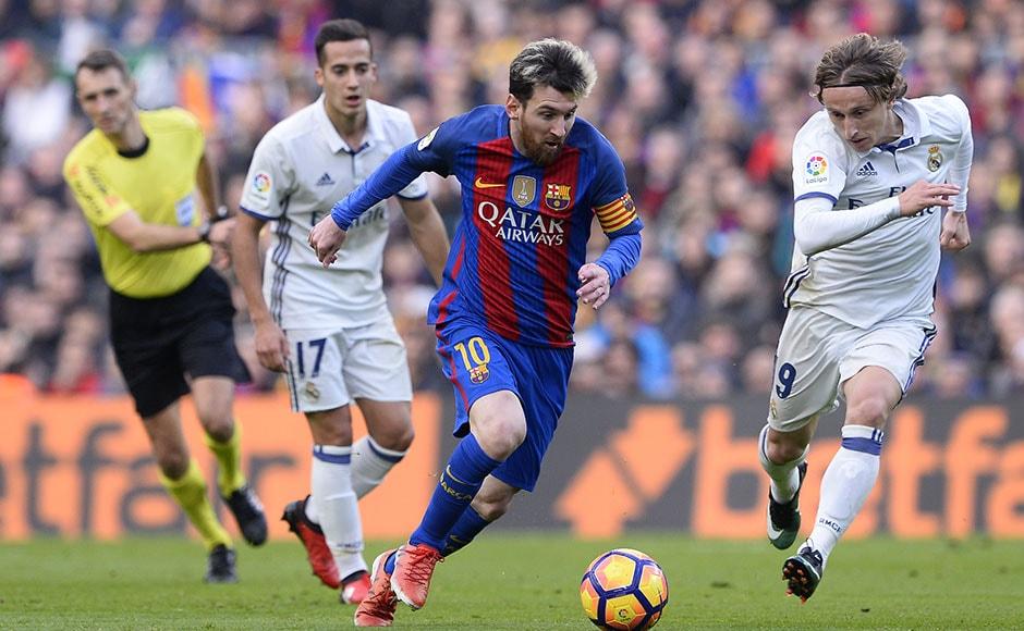 Barcelona's Argentinian forward Lionel Messi (C) vies with Real Madrid's  Croatian midfielder Luka Modric