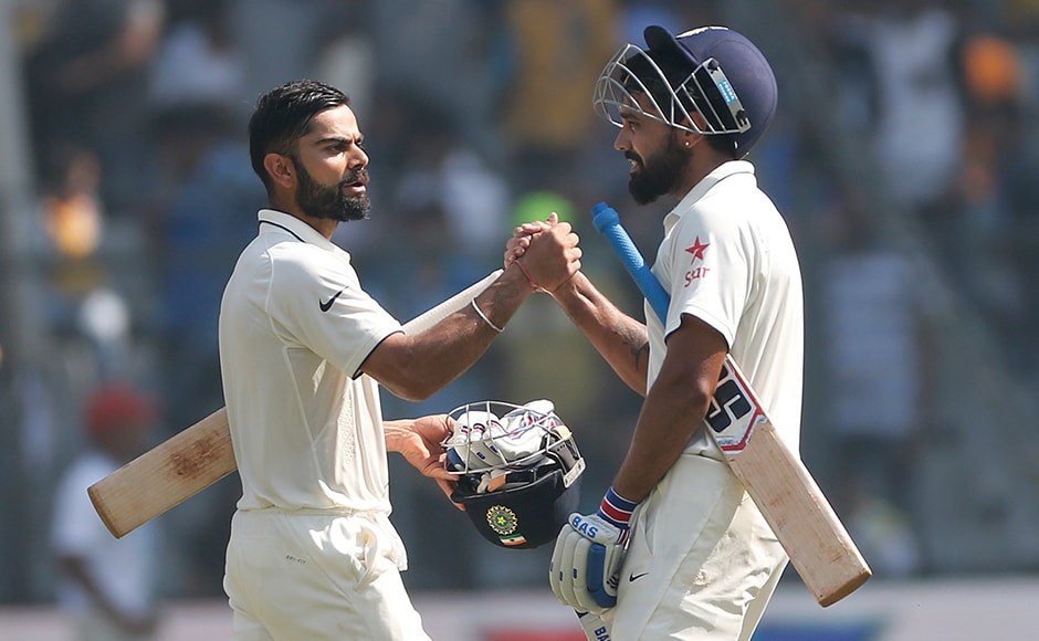 Indian cricket captain Virat Kohli left, greets Murali Vijay on the third day of the fourth cricket test match between India and England in Mumbai, India, Saturday, Dec. 10, 2016. AP