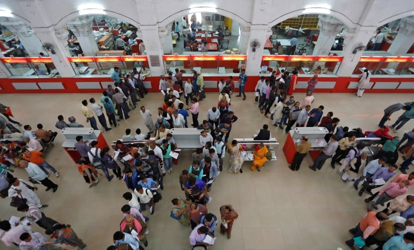 People wait in lines to deposit and withdraw money. Reuters