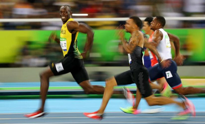 Usain Bolt of Jamaica turns to look at Andre De Grasse of Canada as they compete in the Men's 100m Semifinals at the 2016 Rio Olympics. Reuters