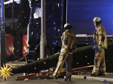 Firefighters look at a toppled Christmas tree after a truck ran into a crowded Christmas market and killed several people in Berlin, Germany, Monday, Dec. 19, 2016.AP