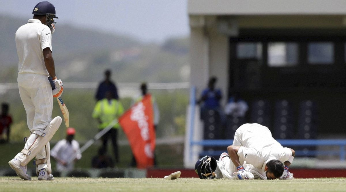 North Sound : India's Ravichandran Ashwin, left, walks towards his captain Virat Kohli as he kisses the field after scoring a double-century during day two of the first cricket Test match against West Indies at the Sir Vivian Richards Stadium in North Sound, Antigua, Friday, July 22, 2016. AP/PTI Photo(AP7_22_2016_000297B)
