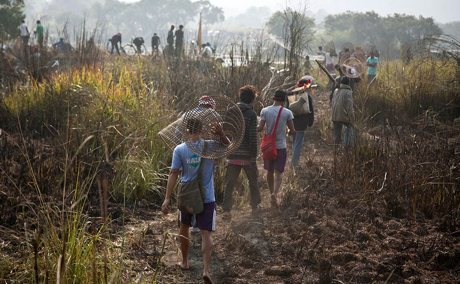 Tribal men walk with their fishing tools to participate in community fishing as part of Bhogali Bihu celebrations in Panbari village, some 50 km east of Guwahation13 January, 2017.