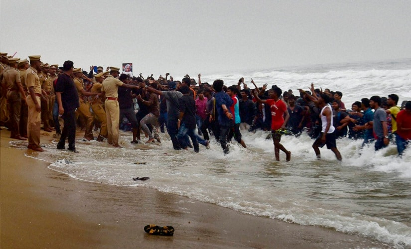 Police try to evict Pro-Jallikattu protesters from the Marina Beach in Chennai on Monday. PTI
