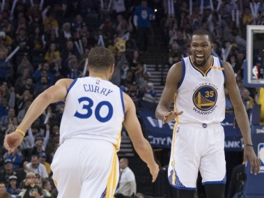 Golden State Warriors Kevin Durant celebrates with Stephen Curry during the third quarter against the Cleveland Cavaliers. Reuters