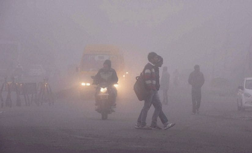 People and vehicles move through a thick blanket of fog in Bhopal on Monday. PTI