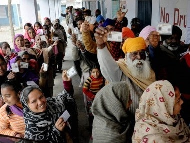 People showing their voter ID cards outisde a polling booth in a village near Amritsar. PTI