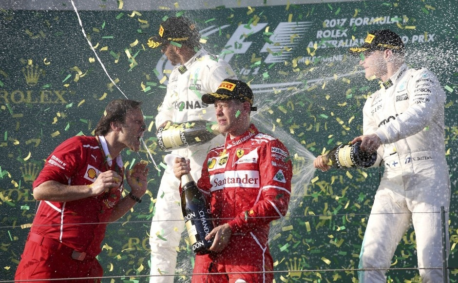 Ferrari team principal Maurizio Arrivabene, left, celebrates along with his driver Sebastian Vettel of Germany as Mercedes driver Lewis Hamilton of Britain, second from left, sprays teammate Valtteri Bottas of Finland, right, after the Australian Formula One Grand Prix in Melbourne, Australia, Sunday, March 26, 2017. Vettel won the race ahead of Hamilton and Bottas. (AP Photo/Rick Rycroft)