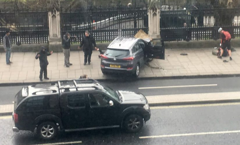 People stand near a crashed car and an injured person lying on the ground, right, on Bridge Street near the Houses of Parliament in London. AP
